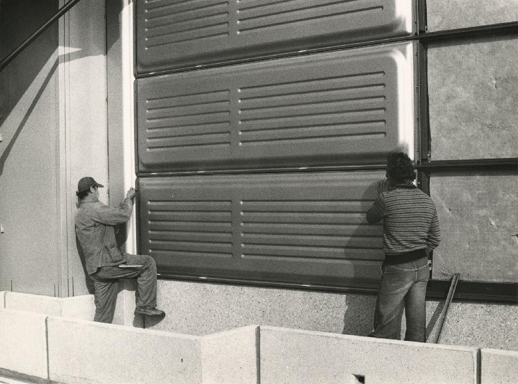 Deux hommes de dos se tenant à chaque extrémité d'un panneau métallique le fixent en bas d'une façade en construction, sous une série d'autres panneaux déjà installés.