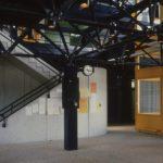 La photographie montre un hall d'entrée de l'école avec au centre un pilier soutenant le treillis bleu en acier, et une cage d'escalier en béton.