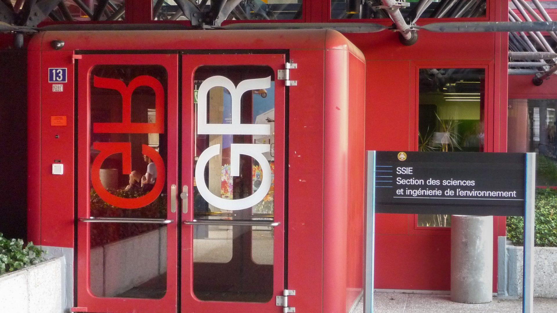 Entrée du bâtiment GR avec textes de signalisation sur les portes et sur un panneau indépendant.