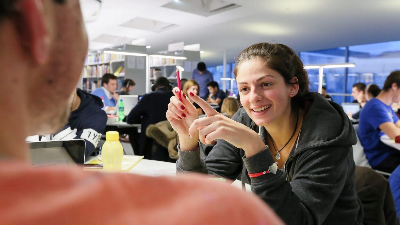 Une étudiante, discutant avec un autre étudiant, durant des révisions au Rolex Learning Center