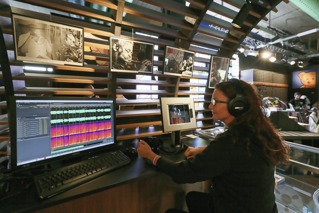 Woman sitting in front of a screen with speakers on her ears