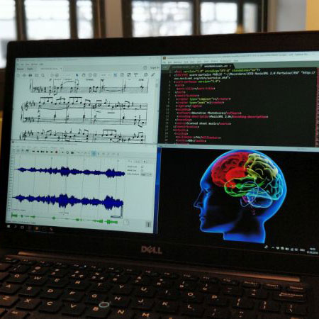 Close up of laptop screen with music score and brain image