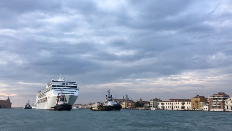 A cruise boat being pulled into Venice by tug boats