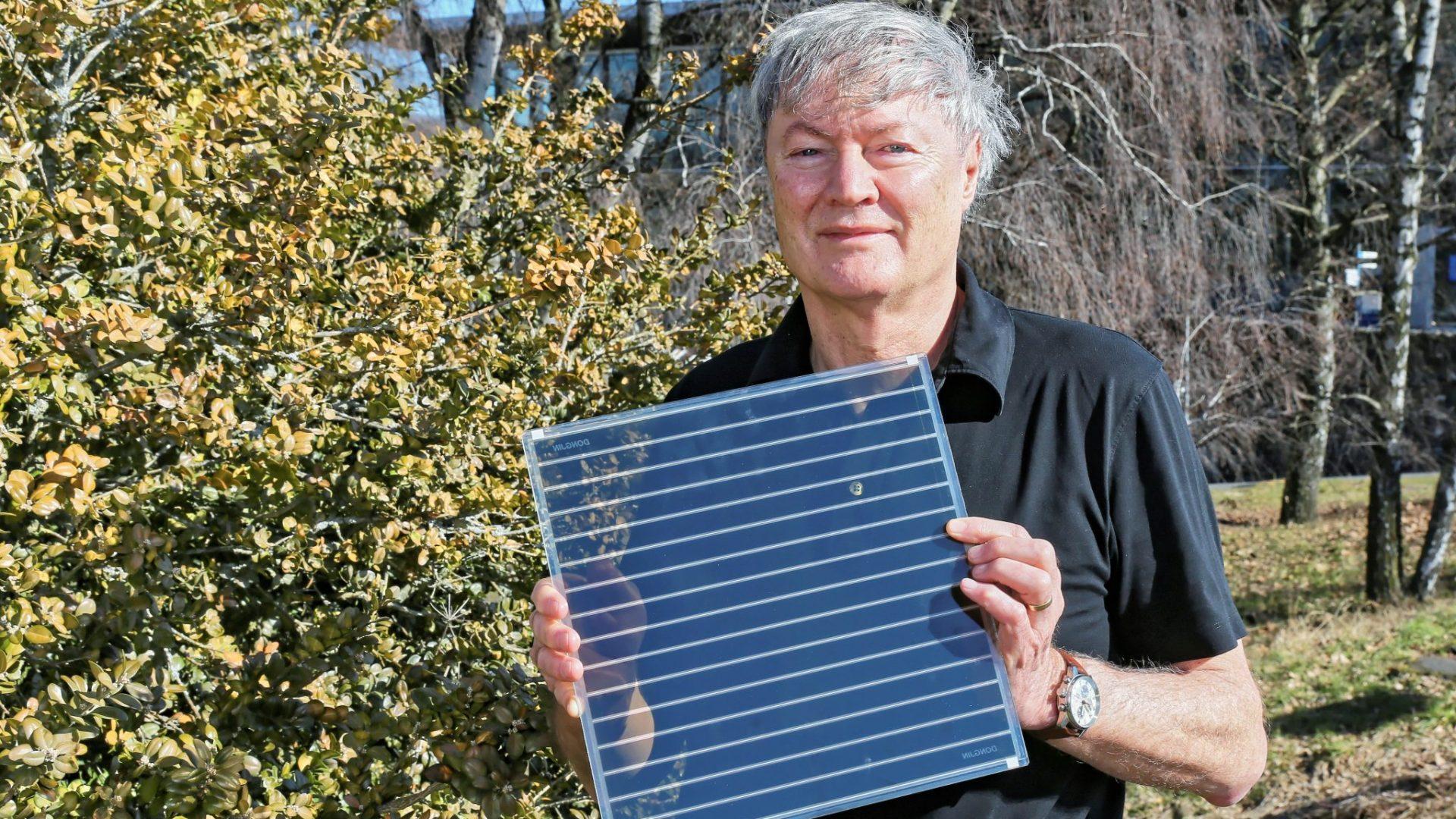 Le professeur Michael Grätzel tient une cellule solaire à pigment photosensible.